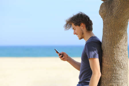 Zijaanzicht van een aantrekkelijke man met behulp van een slimme telefoon op het strand met de zee en de horizon op de achtergrond