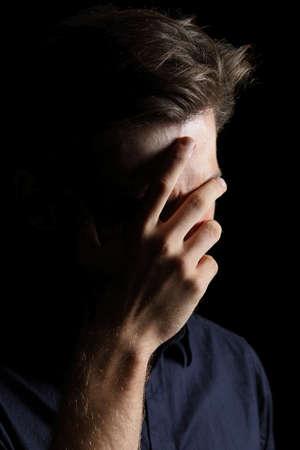 Uomo preoccupato o imbarazzato coprendosi il volto con la mano isolato su uno sfondo nero Archivio Fotografico