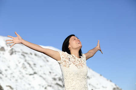 outstretching: Happy woman breathing deep raising arms in winter with sky and a snowy mountain in the background