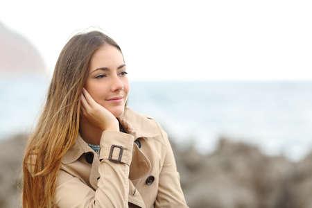 mujer mirando el horizonte: Mujer melancólica hermosa que piensa en invierno en la playa con el mar de fondo
