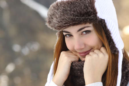 grabbing hand: Beauty woman face portrait warmly clothed in winter holding a scarf outdoors Stock Photo