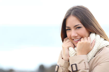 Portrait d'une femme de beauté souriante et attrapant son écharpe en hiver sur la plage