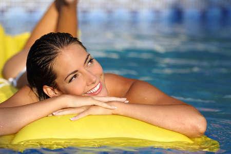 cuerpo perfecto femenino: Muchacha feliz que disfruta las vacaciones de verano en un colch�n en una piscina y que mira la cara mientras pensaba Foto de archivo