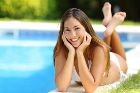Happy girl posing wearing bikini on a pool side in summer vacations with a garden in the background