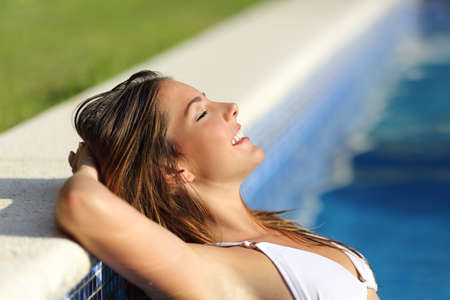 beautiful weather: Side view of a happy woman relaxed in a swimming pool enjoying vacations with a green and blue background Stock Photo