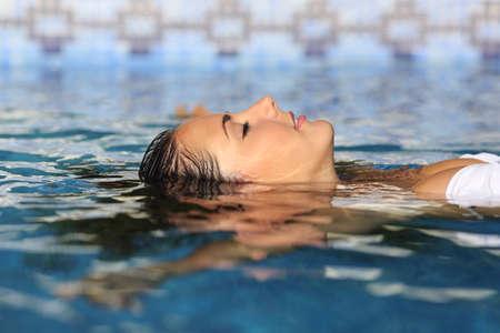 Perfil de una mujer de belleza cara relajada flotando en el agua de una piscina que disfrutan de vacaciones