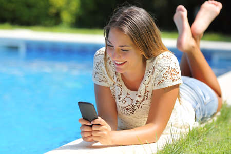 wireless telephone: Teenager girl using a smart phone resting on a pool side with a blue water background