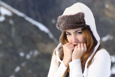 Woman going cold sheltered in winter outdoors in a snowy mountain photo