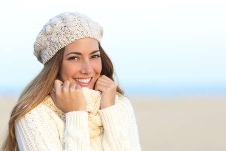 Glimlach van de vrouw met een perfecte witte tanden in de winter met het strand op de achtergrond Stockfoto