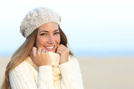 sweet tooth: Woman smile with a perfect white teeth in winter with the beach in the background Stock Photo