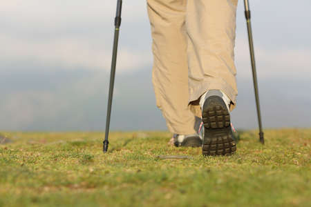 Back view of hiker legs with poles walking on the mountain with an unfocused background photo
