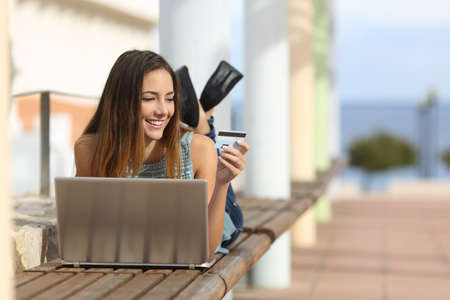holding credit card: Casual girl buying online with a laptop and paying with a credit card lying on a bench outdoors in the street
