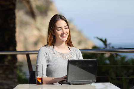 beach front: Happy sitting woman working with her laptop in an hotel terrace on holidays