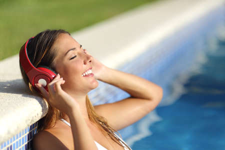 summer vacation bikini: Relaxed woman listening to the music with headphones bathing in a pool