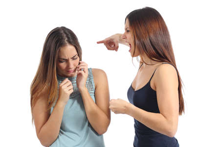 abuse young woman: Angry woman abusing of another scared one isolated on a white background