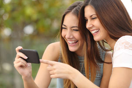 lady: Two funny women friends laughing and sharing social media videos in a smart phone outdoors