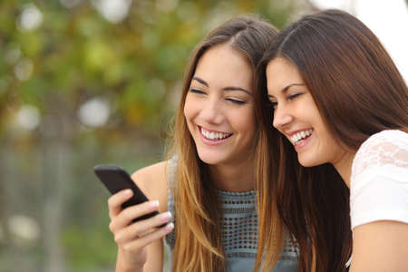 handphones: Two happy women friends sharing social media in a smart phone outdoors in a park
