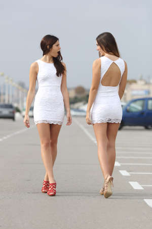Two women walking on the street with the same dress looking each other with hate Stock Photo