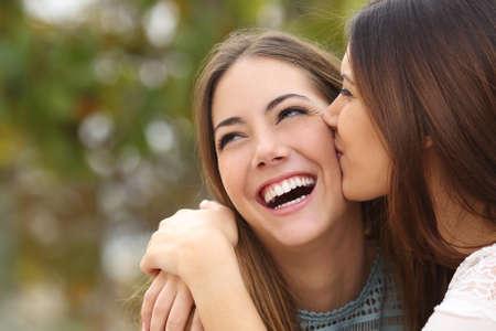 bacio: Donna che ride con denti perfetti, mentre un amico la sta baciando con uno sfondo verde Archivio Fotografico