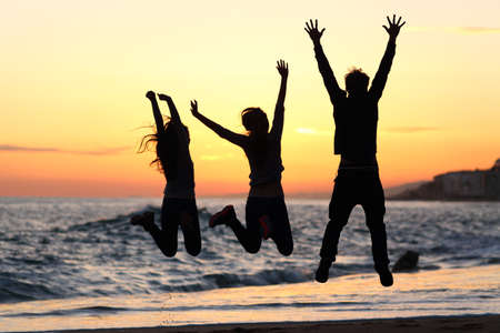 holiday destination: Three friends silhouettes jumping happy and raising arms on the beach at sunset Stock Photo