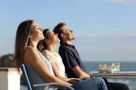 Groep vrienden inademen van frisse lucht in een restaurant op het strand met de oceaan op de achtergrond