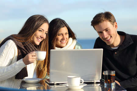 Group of friends watching a laptop in a restaurant terrace on the beach in winter