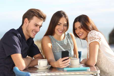medios de comunicaci�n social: Grupo de amigos viendo los medios de comunicaci�n social en un tel�fono inteligente en un restaurante con la playa en el fondo