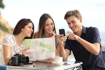amigos: Grupo de amigos de turismo joven que consulta el mapa del GPS en un tel�fono inteligente en un restaurante con la playa en el fondo Foto de archivo