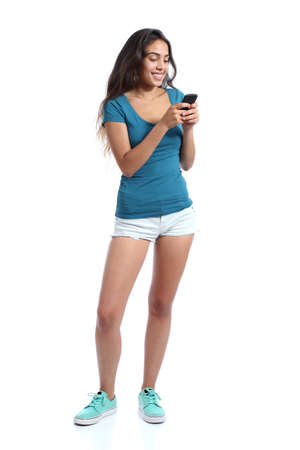 Full body of a teenager girl texting in a smart phone isolated on a white background