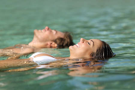 Profile of a couple of tourists swimming in the sea of a tropical resort floating on the turquoise water on summer vacations