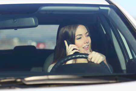 drives: Driver woman driving a car distracted on the phone and looking at side