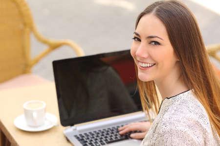 Bovenaanzicht van een gelukkige vrouw met behulp van een laptop in een restaurant en kijken naar de camera