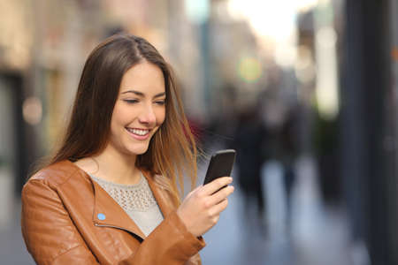 sms: Happy woman using a smart phone in the street with an unfocused background