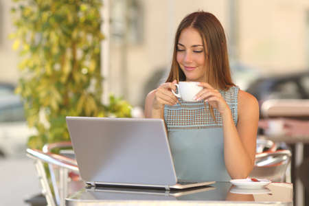 Relaxed woman watching a laptop in a restaurant and holding a cup of coffee Фото со стока