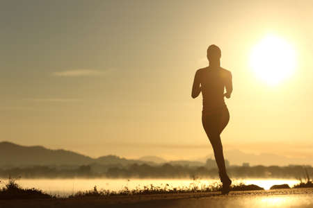 atleta: Runner silueta de la mujer corriendo al atardecer con el sol en el fondo