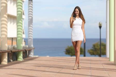 Sexy vrouw lopen en sms op de slimme telefoon in een straat in de buurt van het strand met de zee op de achtergrond Stockfoto