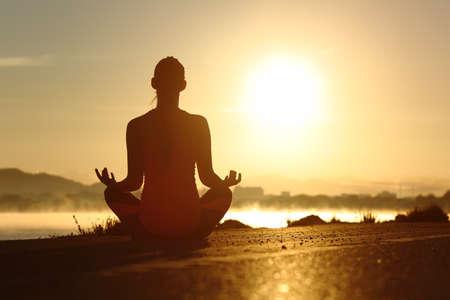 mujer mirando el horizonte: Silueta de una mujer de fitness ejercicio ejercicios de meditación de yoga con el sol en el fondo Foto de archivo
