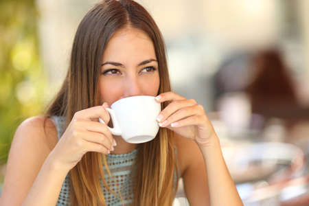 Woman drinking a coffee from a cup in a restaurant terrace while thinking and looking sideways