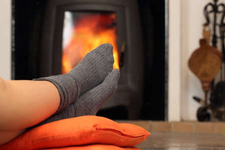 burning fireplace: Woman feet with socks resting near fire place with a warmth background Stock Photo