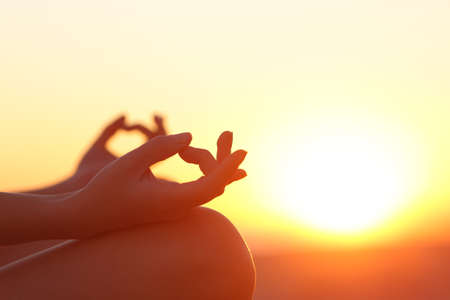 mind: Back light of a woman hands exercising yoga at sunset with a warmth background