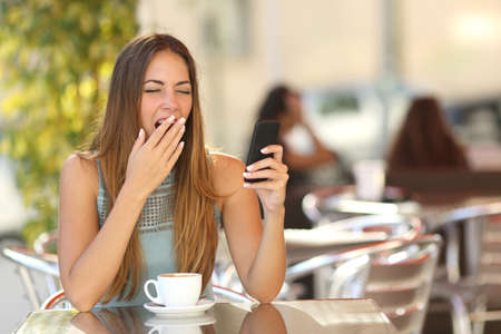 Tired woman yawning while is working on the phone at breakfast in a restaurant Stock Photo