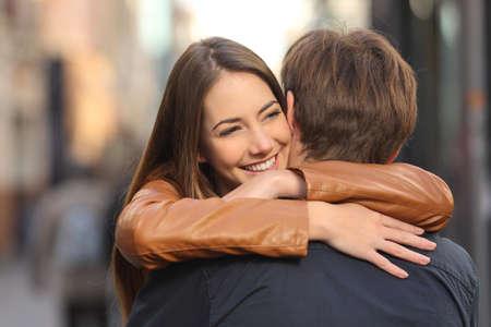 amigos abrazandose: Retrato de una pareja abrazándose feliz en la calle con la cara de la mujer en primer plano Foto de archivo
