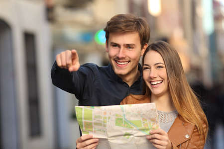 Happy couple of tourists on vacations searching a street in a map and pointing away