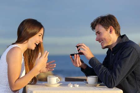 amantes: Novio pidiendo mano de su novia con un anillo de compromiso en un restaurante con el oc�ano en el fondo Foto de archivo