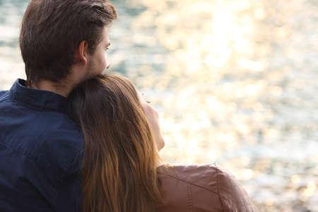 Terug licht van een paar knuffelen en kijken naar de zee bij zonsondergang op het strand