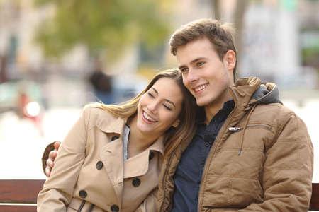 banc de parc: Couple amoureux assis dans un banc étreindre dans un parc urbain en hiver