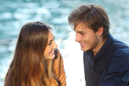 背景に海のある休暇の愛にお互いを探しているカップル