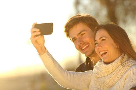 pareja de adolescentes: Pares felices que toman Autofoto foto con un tel�fono inteligente al atardecer en la playa