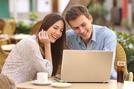 Gelukkige paar kijken naar social media op een laptop in een restaurant met terras