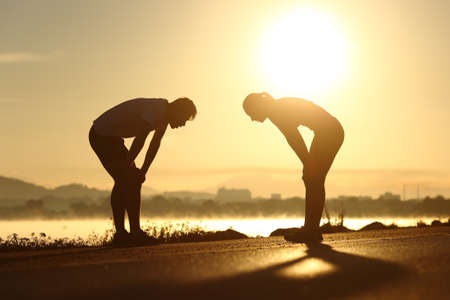 athlete: Side view of a exhausted and tired fitness couple silhouettes at sunset